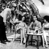 Seated by the side of a huge palm tree, Scotish Irish actor Sean Connery relaxes with Diane Diaz, Jamican model and Shirley Thurllew (right) a former Miss Jamica at Courtleigh Manor Hotel Kingston Jamaica. 26th January 1962